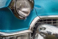 A closeup shot of the front part of a blue car including the lights and the bumper